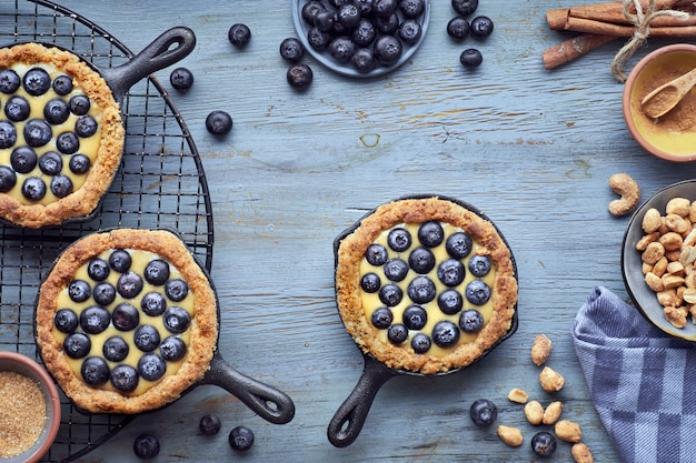 Delicious blueberry tartlets with vanilla custard cream on wood Premium Photo