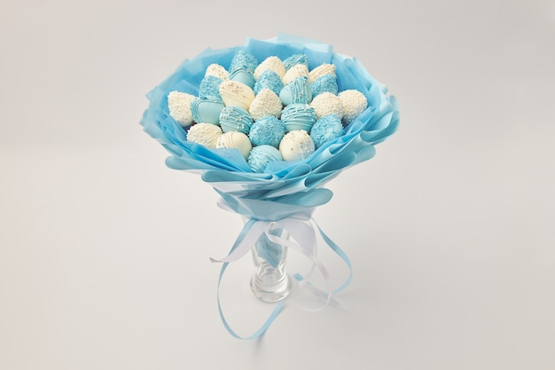 Delicious bouquet of strawberries covered with white and blue chocolate on a white background Premium Photo