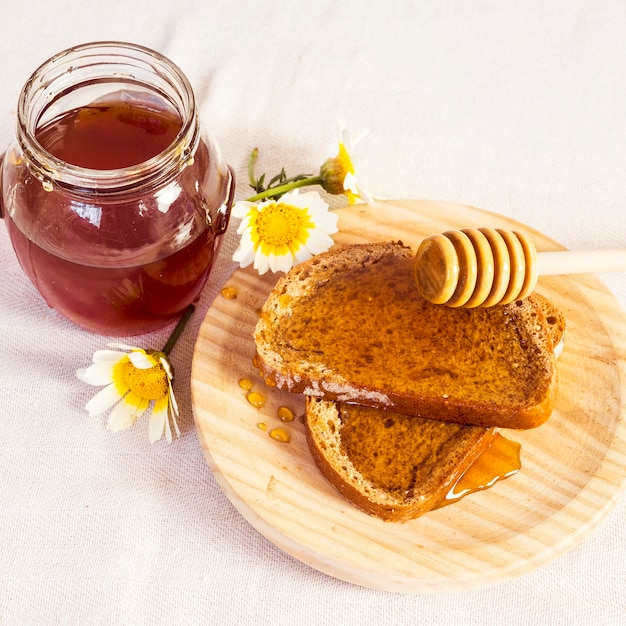 Delicious bread and honey in wooden plate Free Photo