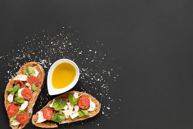 Delicious bread with toppings and olive oil over black background Free Photo