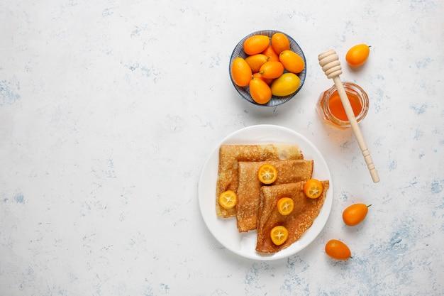 Deliziosa colazione. vacanze ortodosse maslenitsa. crepes con cumquat e honet, vista dall'alto Foto Gratuite