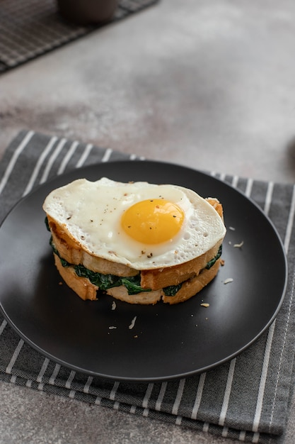 Delicious breakfast sandwich with fried egg, spinach and cheese on a dark plate. close-up Premium Photo