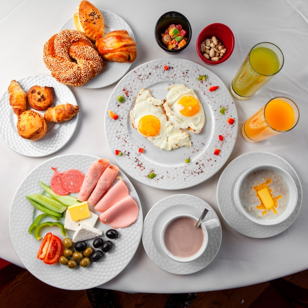 Delicious breakfast in a table with salad, fried eggs and pastry top view on a white background Free Photo