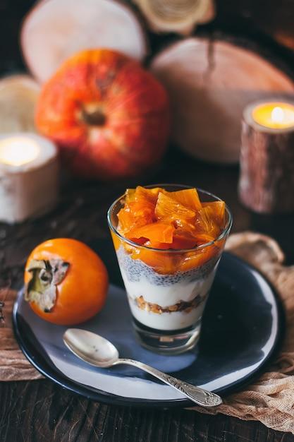 テーブルの上のグラスにチアシードプディングと柿のおいしい朝食 Premium写真