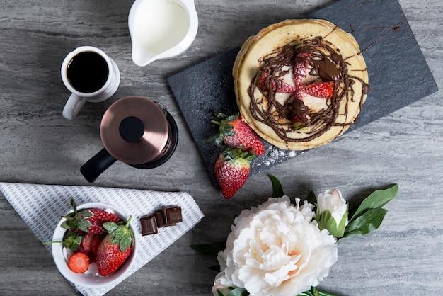 テーブルの上にコーヒー、イチゴとチョコレートのパンケーキとおいしい朝食 無料写真