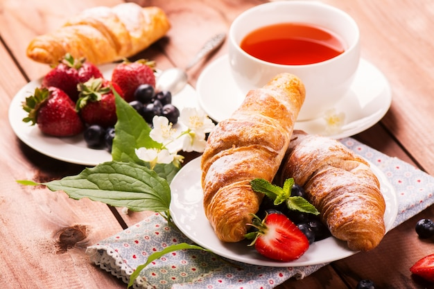Delicious breakfast with fresh croissants and ripe berries on old wooden background Premium Photo