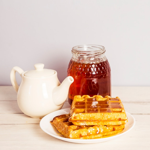 Delicious breakfast with tea; sweet waffle and honey Free Photo