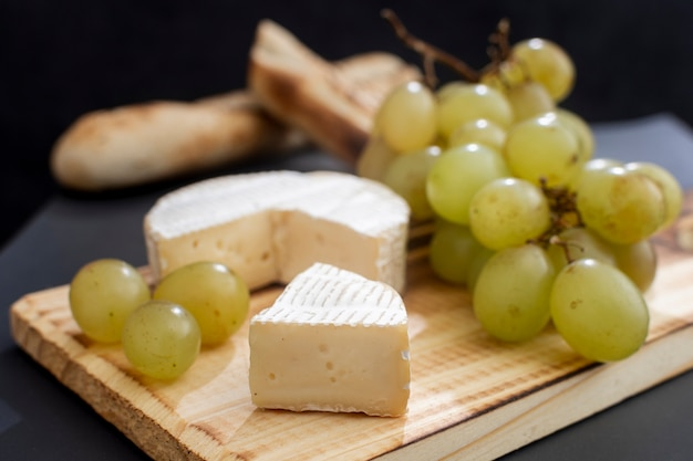 Delicious brie cheese with grapes Free Photo