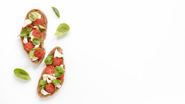 Delicious bruschetta with basil leaves isolated on white surface Free Photo
