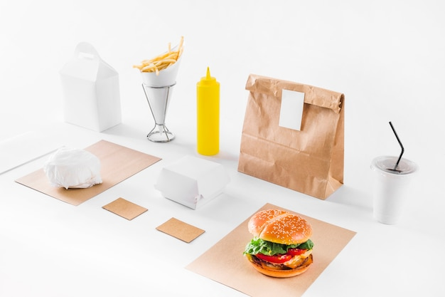 Delicious burger; parcels; disposal cup and sauce bottle on white background Free Photo