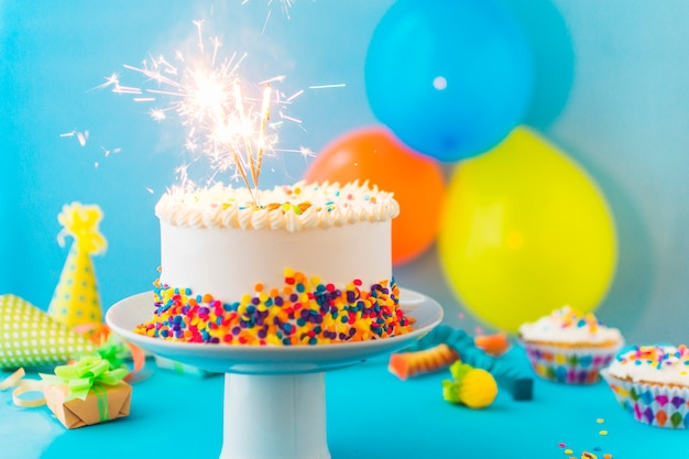 Delicious cake with burning sparklers on cakestand Free Photo