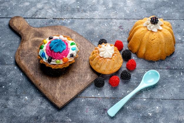 Deliziosa torta con panna e caramelle insieme a torte biscotto ai frutti di bosco sulla scrivania leggera, torta biscotto dolce cuocere caramelle Foto Gratuite