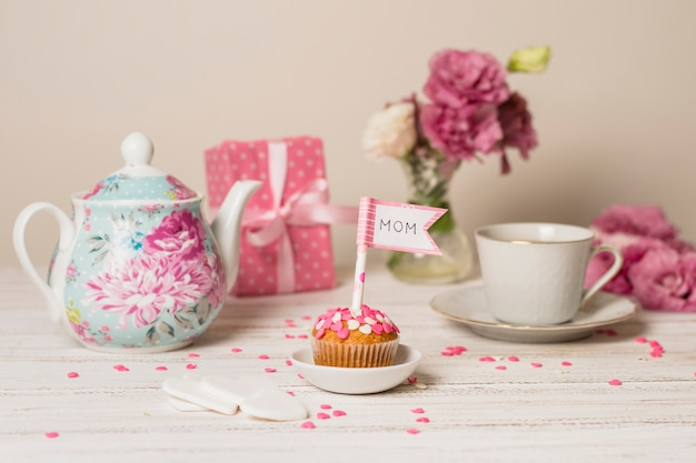 Delicious cake with decorative flag with mom title near teapot, flowers and cup Free Photo
