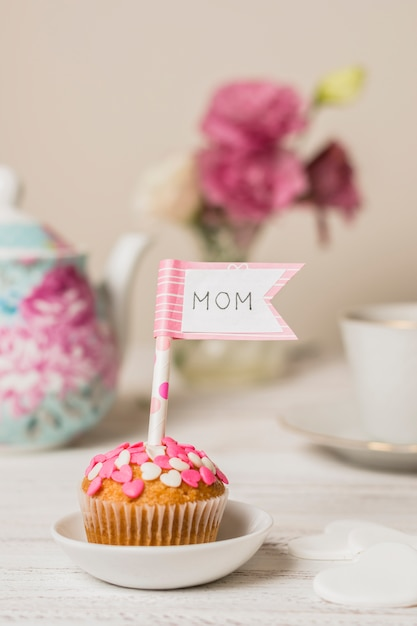 Delicious cake with decorative flag with mom title near teapot and flowers Free Photo