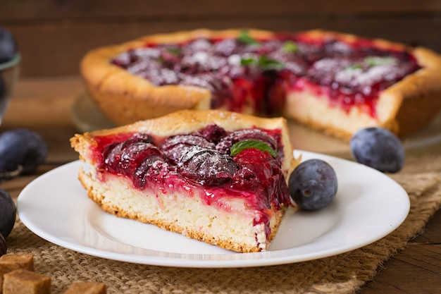 Delicious cake with fresh plums and raspberries Free Photo