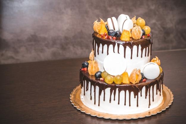 Вкусный торт с фруктами и ягодами украшения на деревянный стол Premium Фотографии