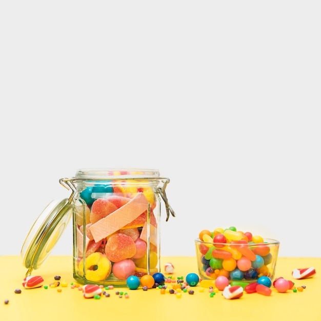 Delicious candies in jar and cup on table Free Photo