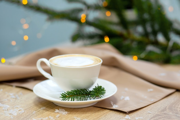 Delicious cappucino coffee cup, fireflies and spruce branches Premium Photo