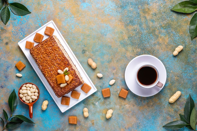 Delicious caramel and peanut cake with peanuts and caramel candies, top view Free Photo