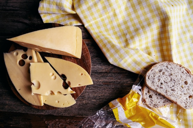 Delicious cheese on wooden board and bread Free Photo