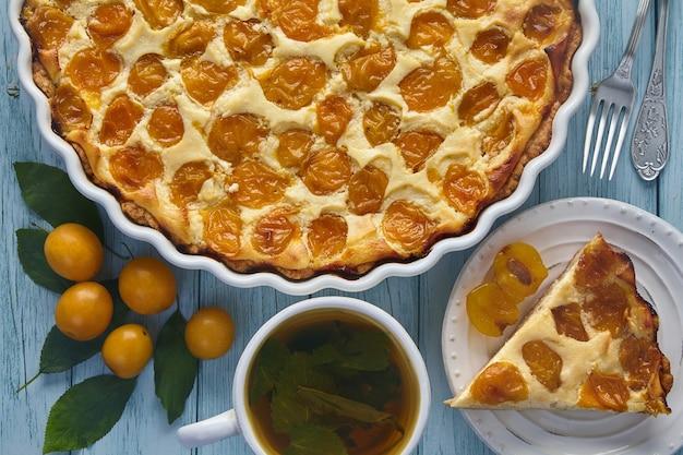 チェリープラムベリーとミントハーブティーに囲まれた青い塗られた木製のテーブルの上のベーキング皿のおいしいチェリープラムパイ。庭での秋の収穫 Premium写真