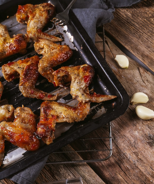 Delicious chicken wings on wooden table Free Photo