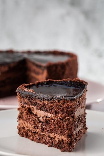大理石の背景にテーブルの上の皿においしいチョコレートケーキ。ペストリーカフェやカフェメニューの壁紙。垂直。 Premium写真