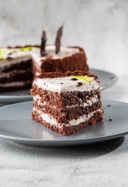 大理石の背景にテーブルの上の皿に白いココナッツクリームとおいしいチョコレートケーキ。ペストリーカフェやカフェメニューの壁紙。垂直。 Premium写真