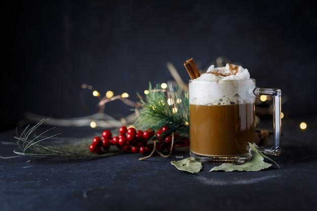 Вкусный рождественский кофе с корицей и пеной, рядом с остролистом на темной поверхности Бесплатные Фотографии