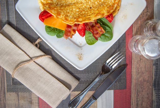 Delicious close up omelette with cheese ,grill tomato.ham,crispy becon and salad Premium Photo
