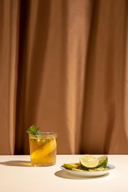 ミントの葉と茶色のカーテンの前にテーブルの上のライムスライスのおいしいカクテルドリンク 無料写真