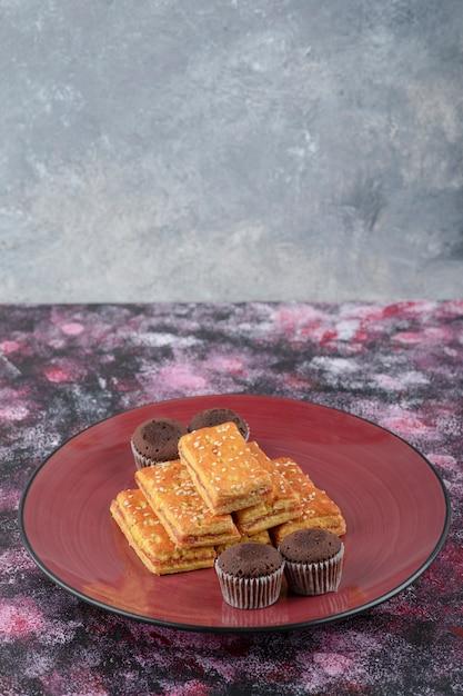맛있는 코코아 비스킷과 빨간 접시에 바삭한 크래커. 무료 사진