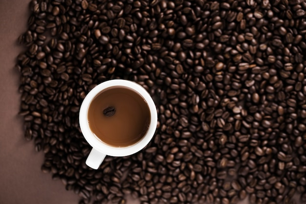 Delicious coffee mug with coffee beans background Free Photo