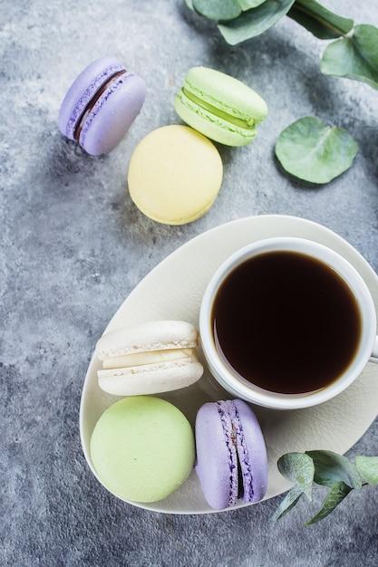 クリームとコーヒーカップのおいしいカラフルなパステルマカロン。マカロンキャンディーとコーヒーブレークシーン Premium写真
