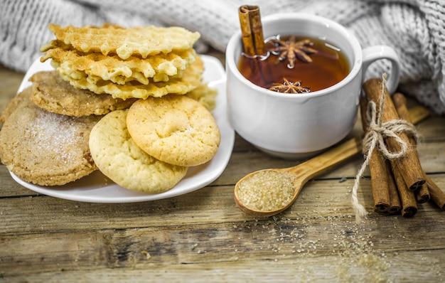 Вкусное печенье и чашка горячего чая с палочкой корицы и ложкой коричневого сахара на дереве Бесплатные Фотографии