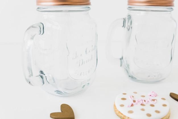 Вкусное печенье и стеклянная банка на белой поверхности Бесплатные Фотографии