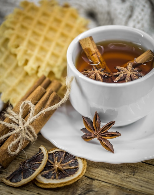 Delicious cookies and cup of hot tea with a cinnamon stick Free Photo