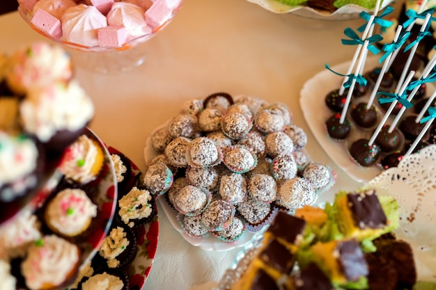 Delicious cookies on the wedding table for guests on the white tablecloth. Premium Photo