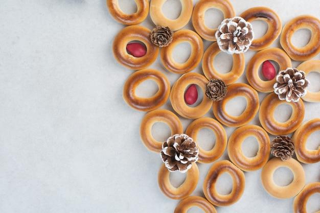 白い背景の上のクリスマスの松ぼっくりとおいしいクッキー。高品質の写真 無料写真