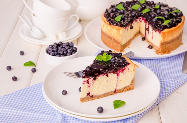 Delicious cream cheesecake with lemon zest and blueberry jam on a plate on white wood