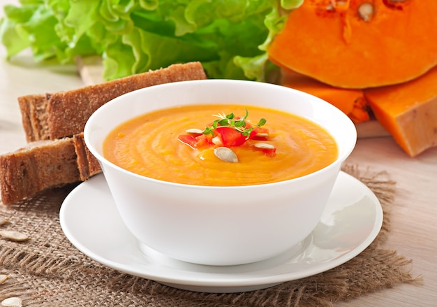 Delicious cream of pumpkin soup in a bowl on wooden table Free Photo