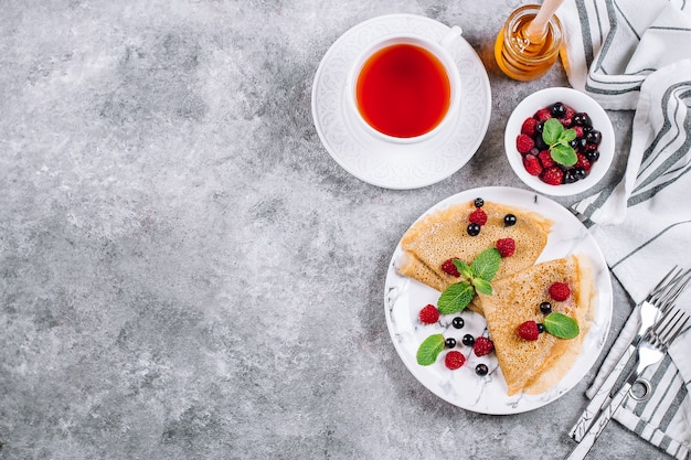 Delicious crepes breakfast on gray concrete table background. pancakes with berry Premium Photo