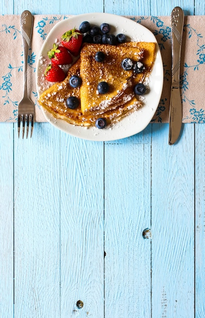 Delicious crepes breakfast with dramatic lighton wood Premium Photo