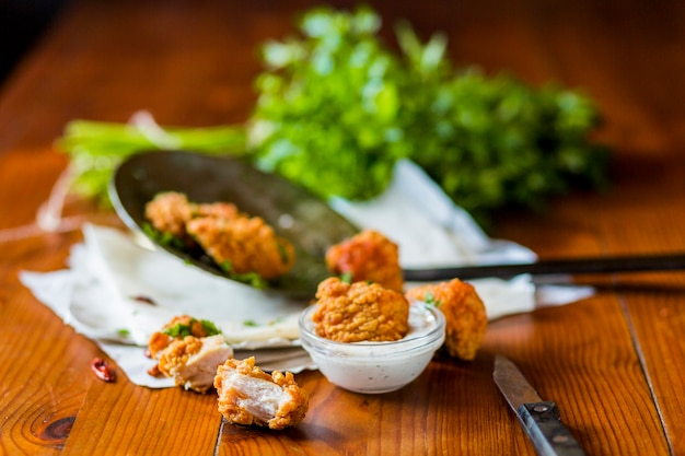 Delicious crispy chicken nuggets with garlic dip on wooden table Free Photo