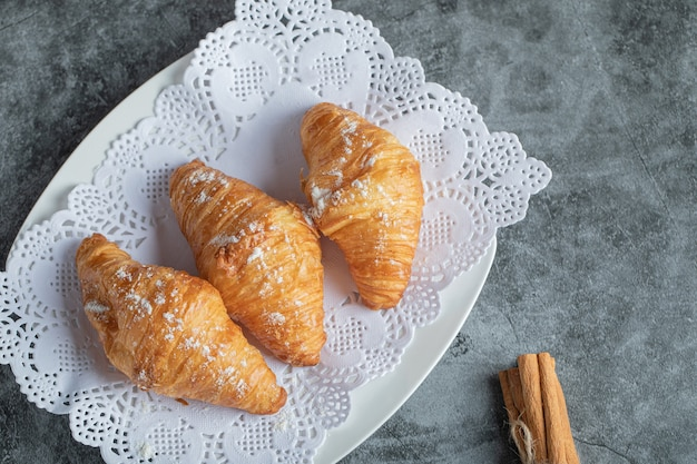 Delicious croissants with cinnamon sticks on gray. Free Photo