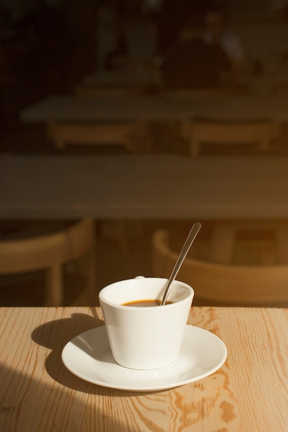 Delicious cup of coffee with saucer on table in caf� Free Photo
