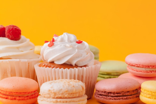 Delicious cupcakes with icing on a yellow Premium Photo