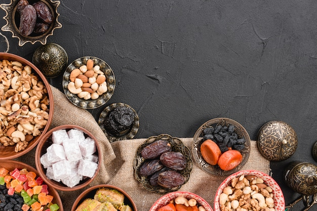 Delicious dates; nuts; dried fruits and sweet lukum on the metallic and earthen bowl on black background Free Photo