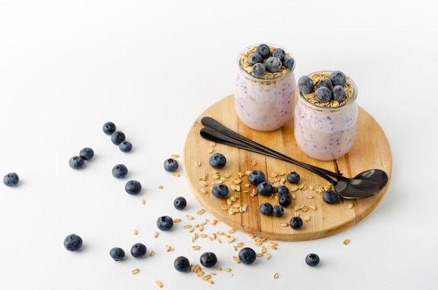 Delicious diet dessert. homemade yogurt with blueberries and oats on wooden board Premium Photo