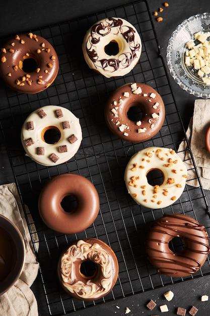 テーブルの上の材料でチョコレート釉薬で覆われたおいしいドーナツ 無料写真